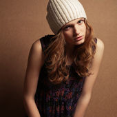 Fashionable model with curly red hair and beige hat posing over — Stock Photo