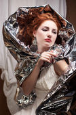 Arty portrait of a fashionable queen-like model with silver foil — Stock Photo