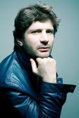 光の上の青いジャケットにファッショナブルなハンサムな男の肖像 — ストック写真