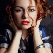 Stock Photo: Beautiful young red-haired model in arty jacket with metal