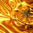 Golden glamour theme with sparkling christmas star on wavy golde — Stock Photo