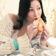 Portrait of a young beautiful woman eating her croissant with st — ストック写真 #17852589
