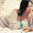 Photo: Portrait of a young beautiful woman eating her croissant with st
