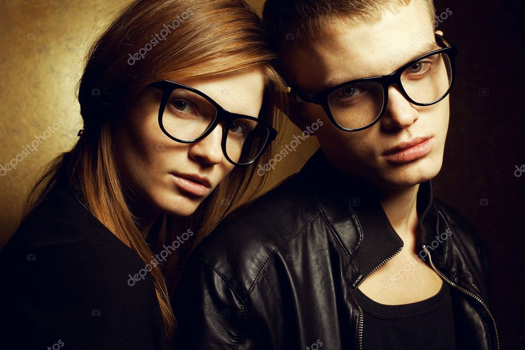 Portrait of gorgeous red-haired fashion twins in black clothes wearing trendy glasses and posing over golden background together. Studio shot. — Stock Photo #18444775