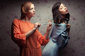 Portrait of two gorgeous girlfriends in blue and orange dresses — Stock Photo