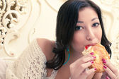 Portrait of a young beautiful woman eating her croissant with st — Stock Photo