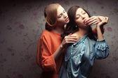 Ritratto di due amiche bellissime in abiti blu e arancione — Foto Stock