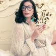 Portrait of a fashionable model in trendy glasses drinking tea o — Stock Photo #20993671