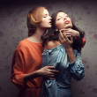 Portrait of two gorgeous girlfriends in blue and orange dresses — Stock Photo #20994097