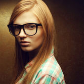 Portrait of a young beautiful red-haired wearing trendy glasses — Стоковое фото