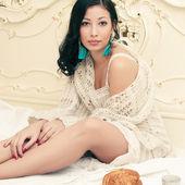 Portrait of a young beautiful brunette having breakfast (tea (co — Stock Photo