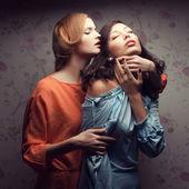 Portret dwóch wspaniałych dziewczyn w niebieskie i pomarańczowe sukienki — Zdjęcie stockowe