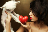 Portrait of a fashionable model with sexy red lips holding red h — Stock Photo