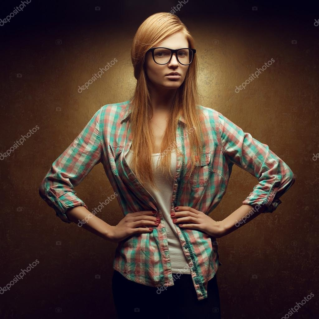 Portrait of a young beautiful red-haired wearing trendy glasses and casual clothes and posing over golden background. Studio shot.  — Photo #20993557