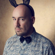 Portrait of a handsome glamourous bald bunny-man posing over gol - Stock Photo
