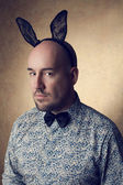 Portrait of a handsome glamourous bald bunny-man posing over gol — Stock Photo