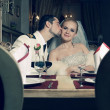 Portrait of kissing bride and groom sitting in a luxurious vinta — Stock Photo