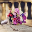 A beautiful wedding bouquet lying on a stone over old house back - Stock Photo