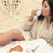 Portrait of a young beautiful brunette having breakfast (tea (co - Stock Photo
