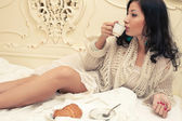 Portrait of a young beautiful brunette having breakfast (tea (co — Stockfoto