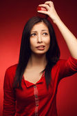 Portrait of a confused student girl posing over red background a — Stock Photo