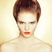 Portrait of a fashionable model with retro hairdo and arty make- — Stock Photo