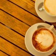 Latte art concept. Two cups with cappuccino (hot coffee with mil — Stock Photo #26446511