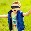 Stylish baby boy with ginger (red) hair in trendy sunglasses and — Zdjęcie stockowe