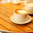 Latte art concept. Two cups with cappuccino (hot coffee with mil — Stock Photo #26446549