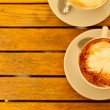 Latte art concept. Two cups with cappuccino (hot coffee with mil — Stok fotoğraf