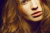 Emotive portrait of a young beautiful girl with curly long ginge — Stock Photo
