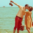 Couple walking on beach. Young happy married hipsters in trendy — Stock Photo #26970219