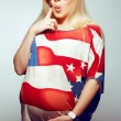 American Mom Concept: Surprised young pregnant woman in american — Stock Photo #27492657
