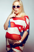 American Mom Concept: Surprised young pregnant woman in american — Stock Photo