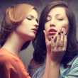 Emotive portrait of two gorgeous girlfriends in blue and orange — Stock Photo #27704559