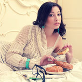 Emotive portrait of a young beautiful woman eating her croissant — Stock Photo