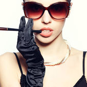 Portrait of a fashionable model in vintage sunglasses with a cig — Stock Photo