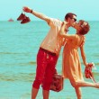 Постер, плакат: Couple walking on beach Young happy married hipsters in trendy
