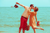 Couple walking on beach. Young happy married hipsters in trendy — Stock Photo