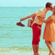Stock Photo: Couple walking on beach. Young happy married hipsters in trendy