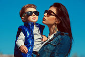 Portrait of fashionable mother hugging her gorgeous baby boy in — Stock Photo
