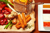 Fried cheese sticks with small meat sausages served with scallio — Stock Photo