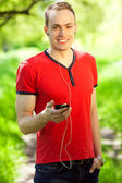 Gadget freak concept. Portrait of a young muscular man in red t- — Stock Photo