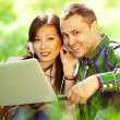 Happy couple of hipsters in trendy casual clothing using a lapto — Stock Photo #46834645