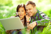 Happy couple of hipsters in trendy casual clothing using a lapto — Stock Photo