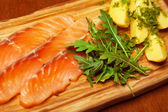 Carpaccio of salmon with boiled potato pieces, ruccola and fenne — Stock Photo