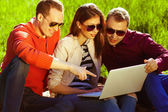 Useful weekend concept. Three happy friends using laptop in park — Stock Photo