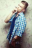 Emotive portrait of handsome man with hipster hairdo smoking — Stock Photo