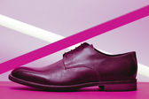 Brown leather men's shoes with violet neon light lamp over laven — Stock Photo