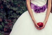 Bride's hands holding red apple - symbol of love - over white dress — Stock Photo